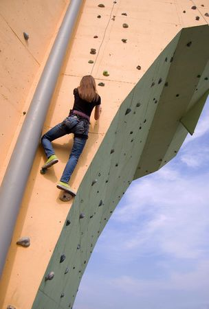 strive for: A girl climbing persistently to the top of the wall with blue sky and clouds