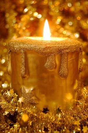 Golden burning candle surrounded by golden starts and sparkles Stock Photo - 5534959