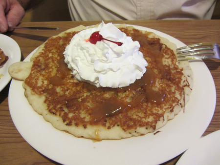 Cinnamon Apple Pancake with Whipped Cream and Cherry Foto de archivo - 120983588