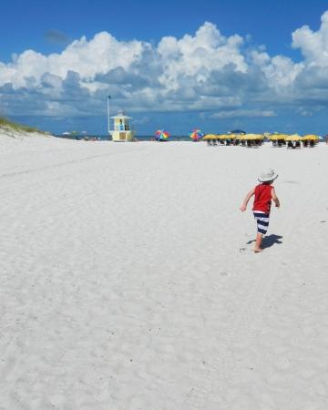 Kleine jongen met rood overhemd die op witte zandstrand Clearwater Beach FL