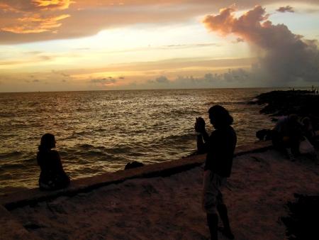 Fotograferen vriendin en de zonsondergang op de Golf van Mexico zeewering