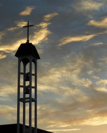 Klokkentoren met kruis bij zonsopgang