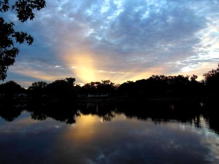 일출 빛의 광선이 호수에 반영