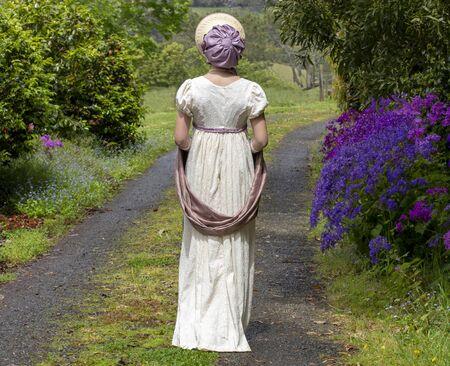 Regency woman walking down a path Stok Fotoğraf