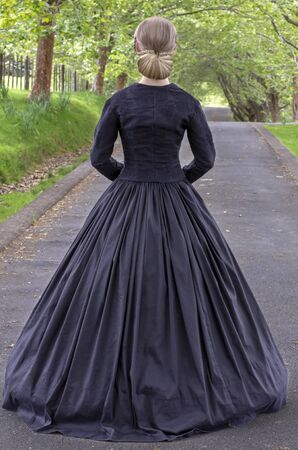Victorian woman in black dress back view