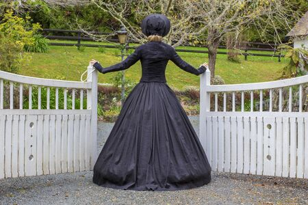 Victorian woman in black dress opening gates Foto de archivo