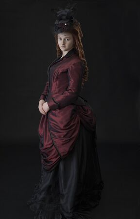 A young Victorian woman in a red and black bustle dress Stock Photo