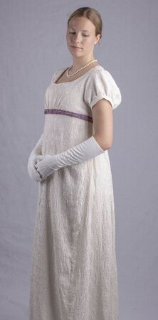 Young woman in a cream embroidered Regency dress 版權商用圖片