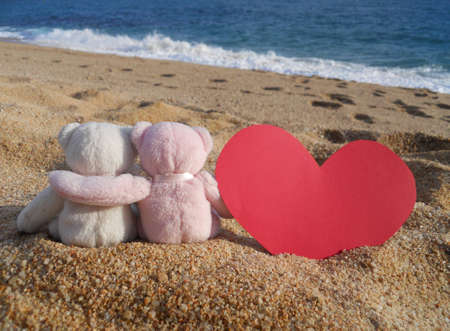 anniversary beach: teddy bears romance (white and pink stuffed animal teddy bears toys with red heart sitting on the beach)