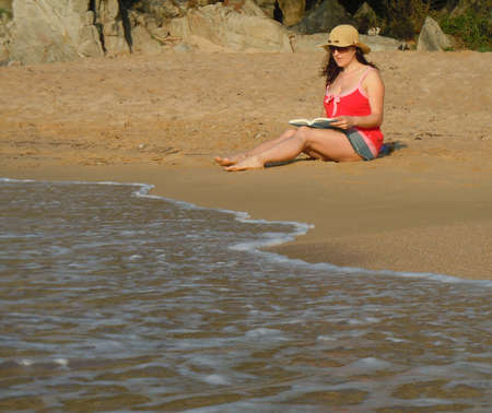 young woman sitting on the beach reading a book photo