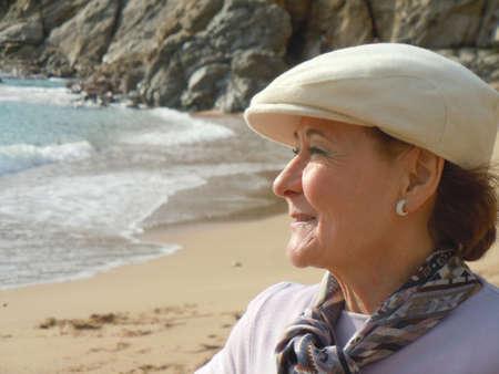 lachende senior vrouw kijken naar de zee Stockfoto