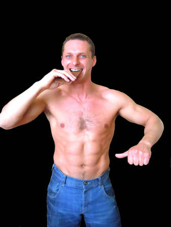 muscle belly: young man with chocolate and smile, pointing at his slim belly Stock Photo