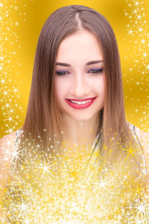 yellow shine: Close-up portrait of a beautiful young brunette woman, she looks at the surprise and smiles; girl with brown eyes and red lips on yellow shine background, gift option; blur effect Stock Photo