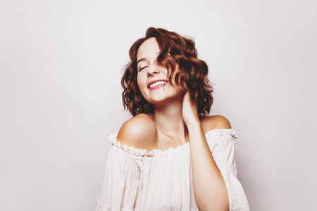 Beautiful studio portrait of  young cheerful woman with curly hair style. Natural beauty concept. Enjoying life
