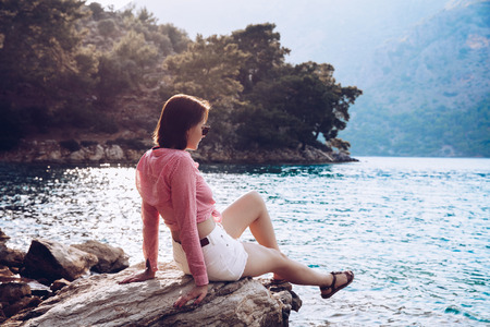 A woman is sitting at ease by the sea .Young girl enjoying blue mediterranean view alone Travel Lifestyle concept adventure vacations outdoor. Melancholy solitude emotions Stock Photo