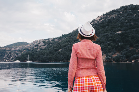 A woman is standing  at ease by the sea .Young girl enjoying blue mediterranean view alone Travel Lifestyle concept adventure vacations outdoor. Melancholy solitude emotions