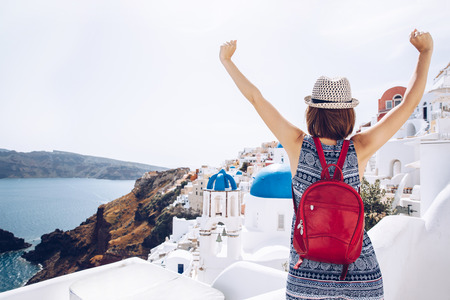 woman traveler with backpack looking at amazing on greek village  wanderlust travel concept, copy space