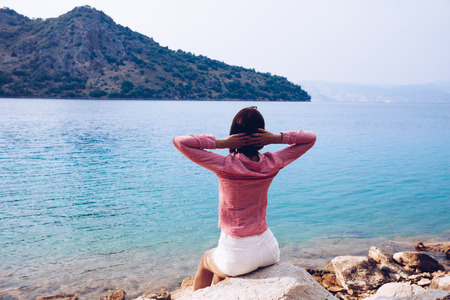 A young woman enjoying a blue mediterranean view alone. Melancholy solitude emotions Stock Photo