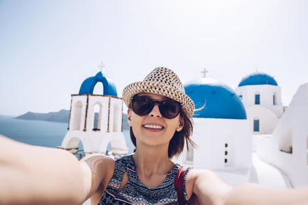 Pretty cheerful young woman holding a smart phone and taking a self portrait on a greek street. Tourism, people, technology concept