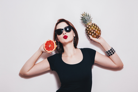 Summer girl portrait. Studio fashionable young woman in sunglasses and on white background holding  pineapple and grapefruit Stock Photo