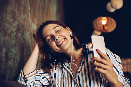 Young woman listen music with headphones and relaxing. Sitting  on cafe, domestic atmosphere. Positive emotion,closed eyes, loft interior