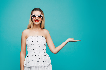 Summer model portrait. Dressed well stylish girl on sunglasses on blue turquoise background. Cheerful young woman on white dress.