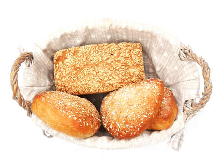 Homemade spelled bread and rolls with oat bran in wicker basket. Isolated on white background.