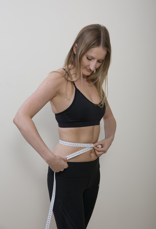 losing control: young woman measuring her waist