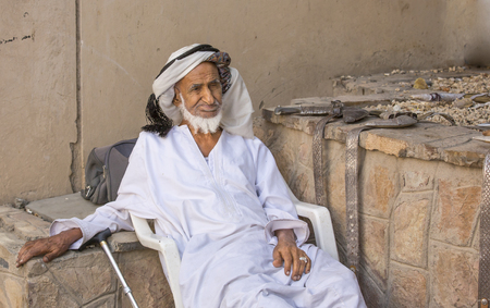 oma: Nizwa, Oma, 24th March, 2017: old Omani man selling old copper cooking dishes at the market