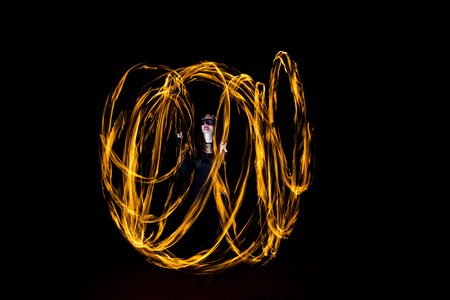 young woman dancing with fire poi, making cirles