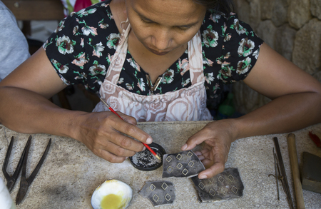 september 9th: Bali, Indonesia, September 9th, 2016: balinese lady making jewellery