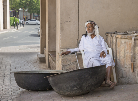 souq: Nizwa, Oman, 24th March, 2017: old Omani man selling old copper cooking dishes at the market