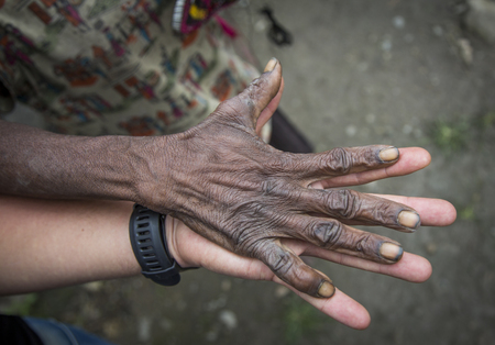 dani: young of a white young man holding a hand of old papuan lady
