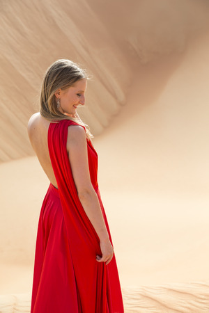 Young and beautiful woman in a red dress in a desert
