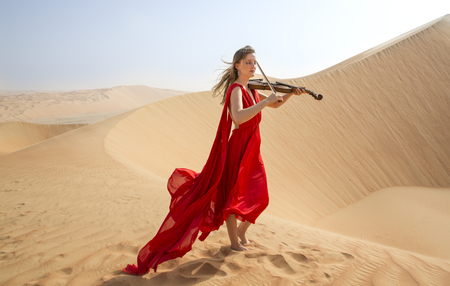Young and beautiful woman in a red dress in a desert with a violin