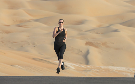woman running on a road in a desert