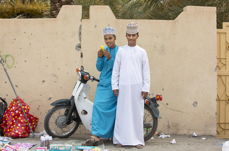 Nizwa, Oman - June 26th 2017: young men in traditional clothing at a toy market on a day of Eid al Fitr, celebration at the end of Holy Month of Ramadan