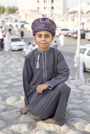 end month: Nizwa, Oman - June 26th 2017: fomani boy in traditional clothing  at Eid al Fitr, celebration at the end of Holy Month of Ramadan Editorial