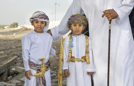 Nizwa, Oman - June 26th 2017: omani boys dressed up for Eid al Fitr day, that is celebrated at the end of Holy month of Ramadan