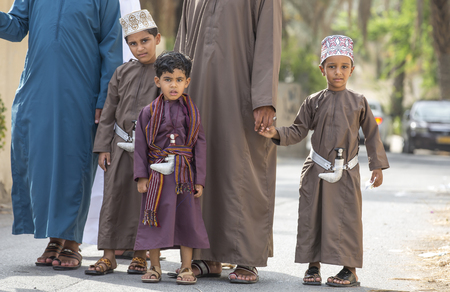 Nizwa, Oman - June 26th 2017: family  in traditional clothing at a toy market on a day of Eid al Fitr, celebration at the end of Holy Month of Ramadan Editorial