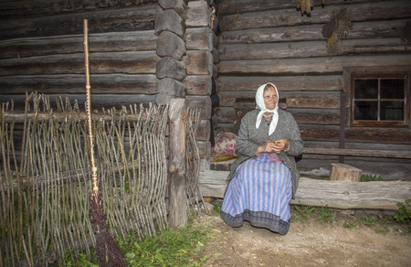 logwood: Tallinn, Estonia, May21th, 2014: old woman outside traditional house knitting