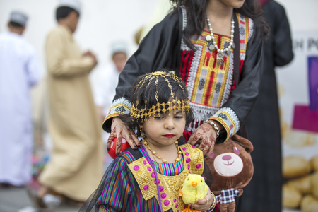 Nizwa, Oman - June 26th 2017: little girl in traditional outfit, with her mother at a toy market on a day of Eid al Fitr