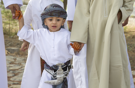 end month: Nizwa, Oman - June 26th 2017: omani kid dressed for Eid al Fitr day, that is celebrated at the end of Holy month of Ramadan Editorial