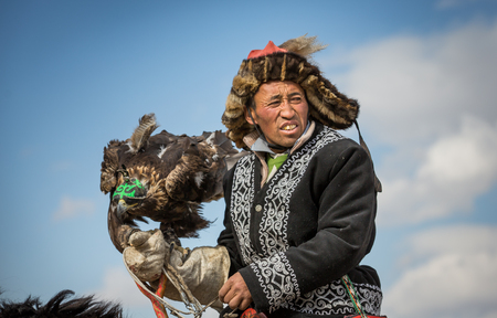 BAYAN ULGII, MONGOLIA - CIRCA OCTOBER 2015: Kazakh man in traditional clothing on his horse Stok Fotoğraf - 81828229