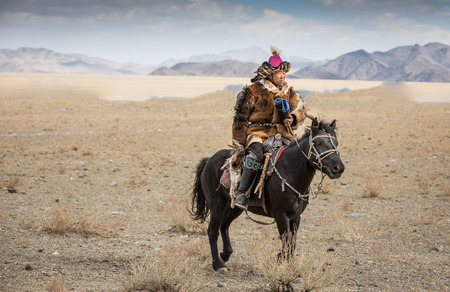 BAYAN ULGII, MONGOLIA - CIRCA OCTOBER 2015: Kazakh man in traditional clothing on his horse Stok Fotoğraf - 81828276