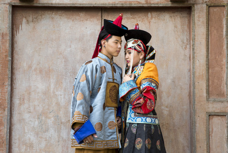 mongolian couple in traditional outfit near old Temple in Ulaanbaatar