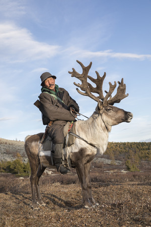 tsaatan man, dressed in a traditional deel, traveling with his reindeers in a taiga of northern Mongolia Stock Photo