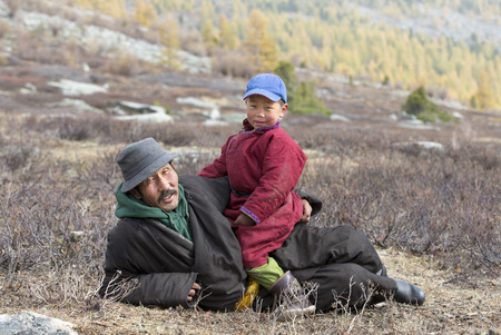 tsaatan boy and his grandfather dressed in a traditional deels resting in nature