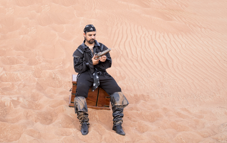 black pirate with a gun and treasure chest in a desert