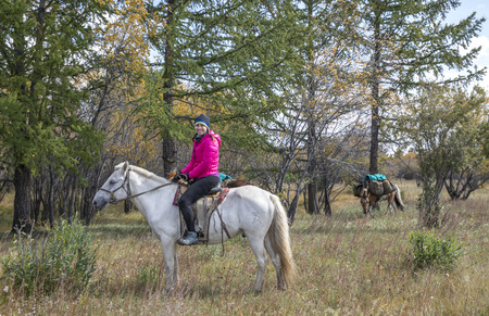 young woman on a horse traveling though taiga in Northern Mongolia